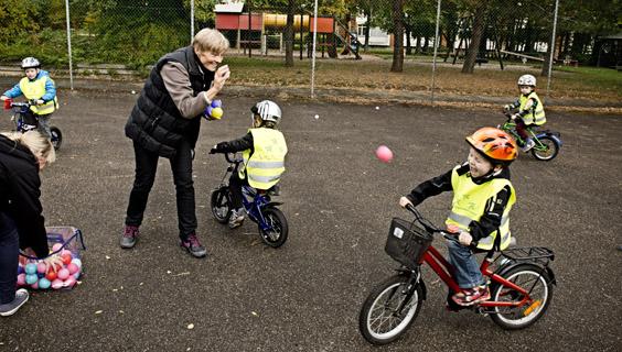 Voksen kaster bolde efter cykelkurve hos børn under cykelleg i den integrerede institution Valnødden i Hvidovre.